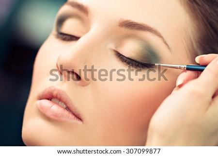 Make-up artist applying liquid eyeliner on model's eyes, close up - stock photo