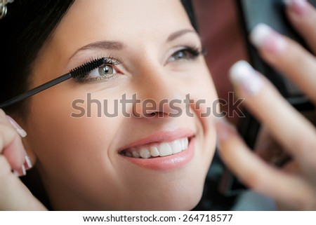 Make-up artist applying liquid eyeliner with brush, close up, shallow depth of field - stock photo