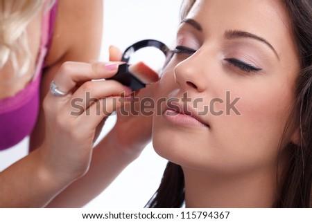 make-up artist applying make-up on woman, close up - stock photo