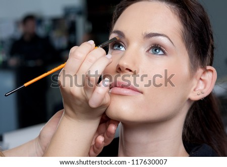 Make up artist applying make up to a fashion model / bride - stock photo