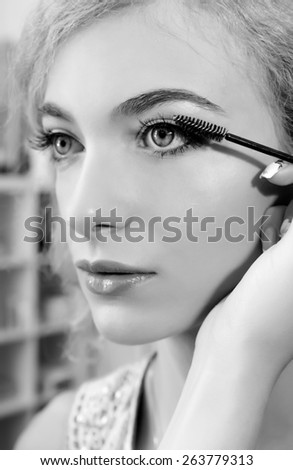 Make-up artist applying mascara  on model's eye, close up. Black and white - stock photo