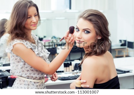 Make-up artist applying powder with a brush on model's cheeks, selective focus on model looking at camera - stock photo