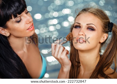 Make-up artist applying rouge on model's cheek, outdoor at summer beach - stock photo