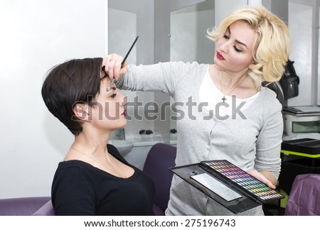 Make-up artist in the studio doing makeup beauty girl - stock photo