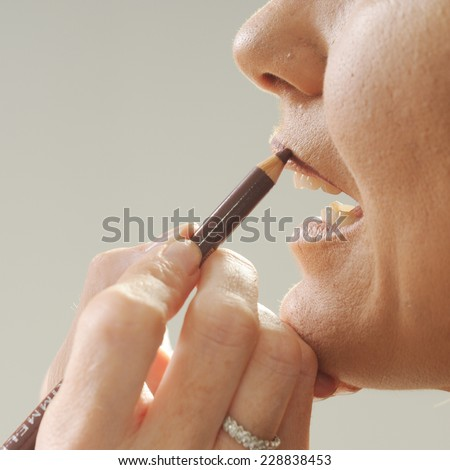 make up artist's hand close up applying lips line with a pencil to the model's mouth - stock photo