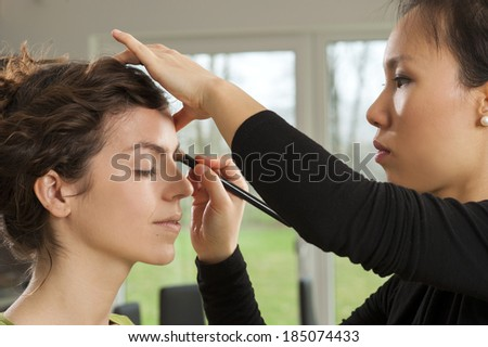Make up artist working on her models look - stock photo