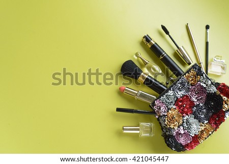 make up bag with cosmetics and brushes on green background. top view. copy space. - stock photo