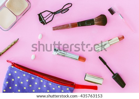 Make up bag with cosmetics on pink background - stock photo