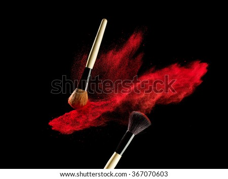 Make-up brush with red powder explosion isolated on black background - stock photo