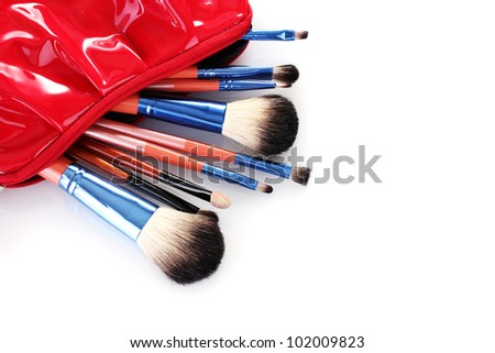 make-up brushes in cosmetics bag isolated on white - stock photo