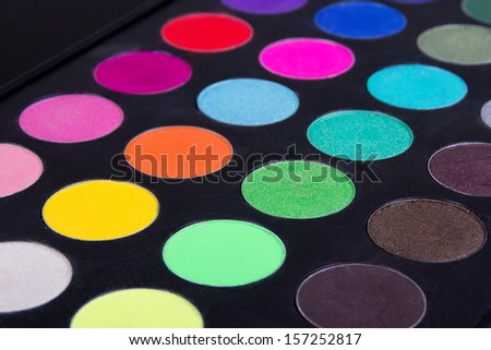 Make up colorful eyeshadow palettes over black background - stock photo