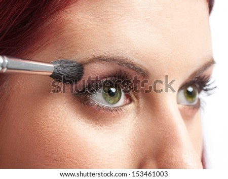 Make-up concept. Close-up image of green eyes woman applying makeup with pencil / brush.  - stock photo
