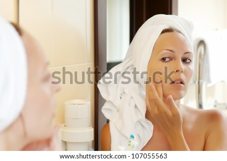 Make-up & cosmetic. Woman in white towel applying skin foundation at bathroom - stock photo