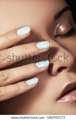Make-up & cosmetics, manicure. Close-up portrait of beautiful woman model face with clean skin on white background. Natural skincare beauty, clean soft skin, manicure. Suntan girl with sky blue nails  - stock photo