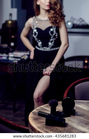 Make-up on a wooden table with a girl in a black dress in the background, elegant outfit - stock photo