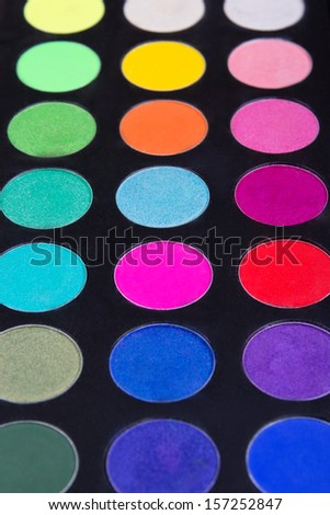 make-up palette of colorfully eyeshadows over black background - stock photo