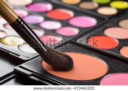Make-up process starts with the brush for foundation dabbing blusher for cheeks. Special cosmetics for giving the skin a beautiful blush. - stock photo