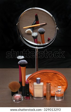 Make up products with oval mirror on vanity table - stock photo