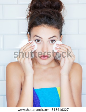 Make up removal concept, young attractive woman covered with towel  with cotton pads - stock photo