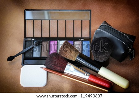 Make-up tools set including eye shadow, make-up brushes, eyebrow pencil, small bag and sponge. - stock photo