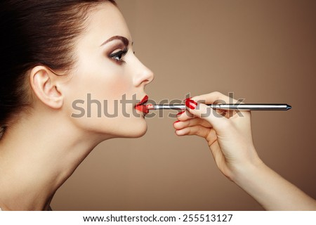 Makeup artist applies lipstick. Beautiful woman face. Perfect makeup - stock photo