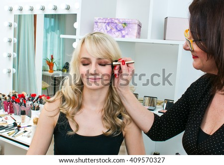 Makeup artist applying eyeliner on attractive womans eyes in salon - stock photo