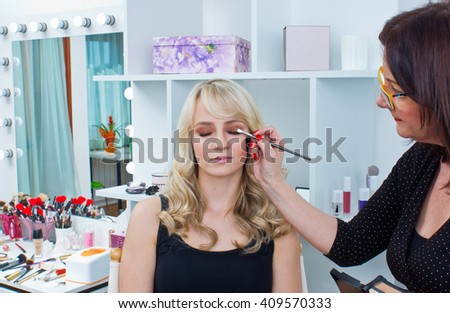 Makeup artist applying eyeshadow on attractive womans eyes in salon - stock photo