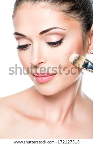 Makeup artist applying liquid tonal foundation  on the face of the woman - stock photo