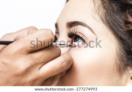 Makeup artist applying mascara on a lady inside a beauty parlor. Close up. - stock photo