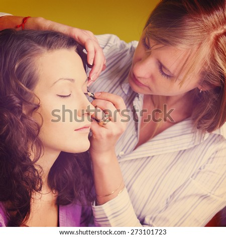makeup artist is applying cosmetics on model face - stock photo