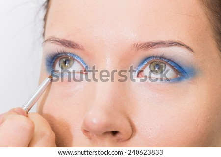 Makeup artist paints the eyebrows model. painting of eyebrows. Makeup artist in a beauty salon doing make-up special brush. Dressing room, fashion, creativity and beauty. - stock photo