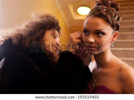 makeup artist puts a necklace around his neck a beautiful girl - stock photo
