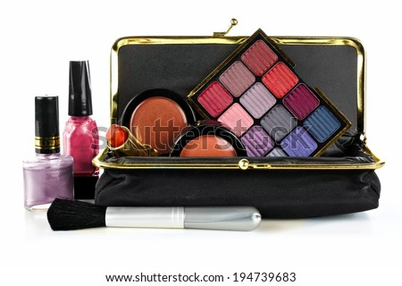 Makeup bag with assorted cosmetics over a white background - stock photo