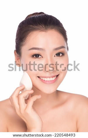 Makeup beauty Asian woman applying blush on face. Make up girl looking at camera putting make-up on cheeks. Model face of beautiful woman with foundation on skin cosmetics isolated on white.  - stock photo