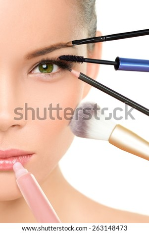 Makeup beauty transformation concept face makeover - Asian woman with many brushes against one side of the face putting mascara, blush and lip gloss - stock photo