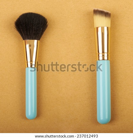 Makeup brush and cosmetic blush. On a beige background - stock photo