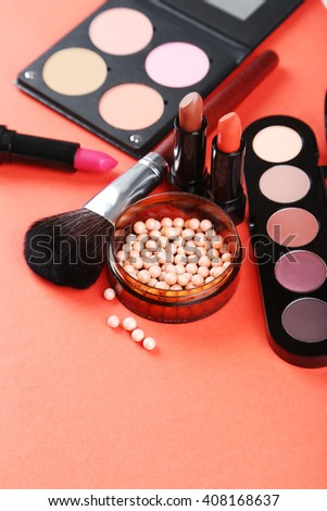 Makeup brush and cosmetics on a red background - stock photo