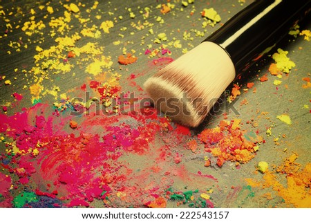 Makeup brush close-up with colorful powder. Toned image - stock photo