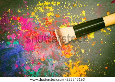 Makeup brush on a background with colorful powder. Top view - stock photo