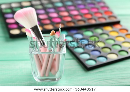 Makeup brush set with palette on a mint wooden table - stock photo