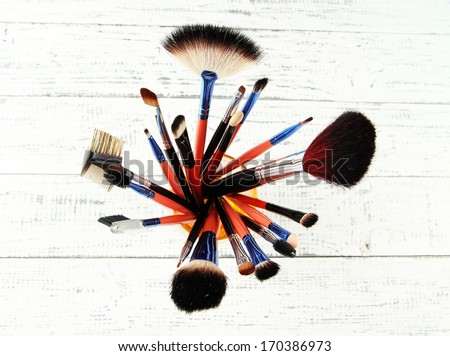 Makeup brushes in glass on wooden background - stock photo