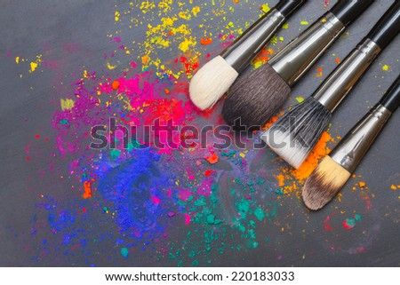 Makeup brushes on a background with colorful powder. Makeup concept - stock photo