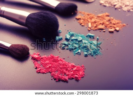 Makeup brushes on background with colorful powder. Crushed eyeshadow on black background. Abstract background. Selective focus, color toning.  - stock photo
