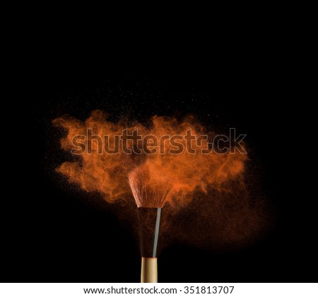 Makeup brushes on black background with colourful powder splash close up. - stock photo