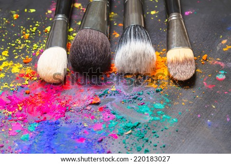 Makeup concept. Makeup brushes on a background with colorful powder - stock photo