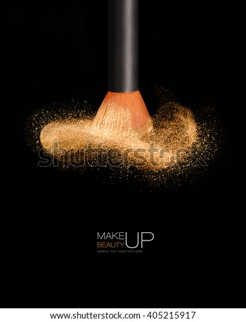 Makeup concept with a single professional makeup brush with glowing face powder isolated on black background with copy space and sample text - stock photo