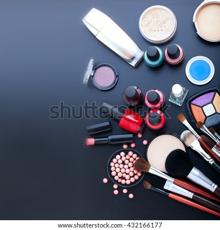 Makeup cosmetics products on dark background with copy space. Cosmetics make up artist objects: lipstick, eye shadows, nail polish, powder, tools for make-up. Top view mock up square. Selective focus - stock photo