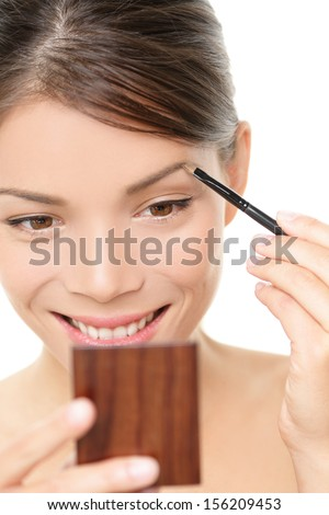 Makeup girl putting eyebrow color looking in pocket mirror. Smiling happy young beauty woman applying make-up with eye brow brush holding pocket mirror isolated, white background. Asian Caucasian girl - stock photo