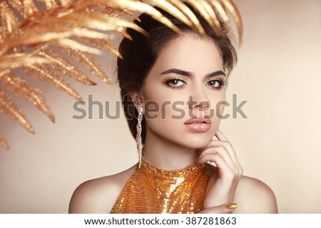 Makeup. Golden jewelry. Beautiful girl with makeup isolated on beige background. Eye make-up and sensual lips. Stare. Elegant hairstyle. Manicure nails.  - stock photo