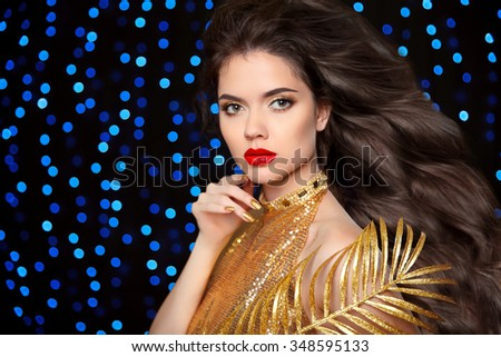Makeup. Hairstyle. Beautiful brunette girl. Gold Fashion Model in elegant golden Dress. Lady with long healthy hair posing over blue holiday lights background. - stock photo